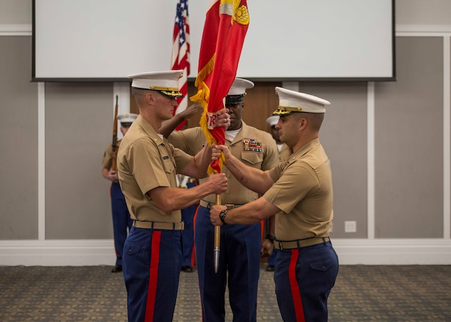 Major Michael Valenti, the outgoing Commanding Officer for Recruiting Station (RS) Jacksonville, hands over the unit colors to Maj. Joseph Gill, the oncoming Commanding Officer for RS Jacksonville, during the RS Jacksonville change of command ceremony in Jacksonville, Florida, June 22, 2018. During the ceremony, Maj. Michael Valenti, the outgoing commanding officer for RS Jacksonville, will relinquish his command to Maj. Joseph Gill. (U.S. Marine Corps photo as Lance Cpl. Jack A. E. Rigsby)