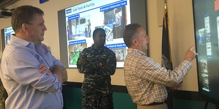 IMAGE: DAHLGREN, Va. (June 28, 2018) - Naval Surface Warfare Center Dahlgren Division (NSWCDD) Chief Innovation Officer Nelson Mills demonstrates the Bluescape collaboration software for James Geurts, Assistant Secretary of the Navy for Research for Development and Acquisition, during his tour of the NSWCDD Innovation Lab (iLab). NSWCDD Commanding Officer Capt. Godfrey 'Gus' Weekes looks on as Mills explains how the virtual workspace allows for real-time cloud-based collaboration. Virtualization and directed energy were among the briefs NSWCDD scientists and engineers presented to Geurts who also observed a laser demonstration. As the Navy's acquisition executive, Geurts has oversight of an annual budget in excess of $60 billion and is responsible for equipping and supporting Sailors and Marines with the best platforms, systems and technology as they operate around the globe in defense of the nation.