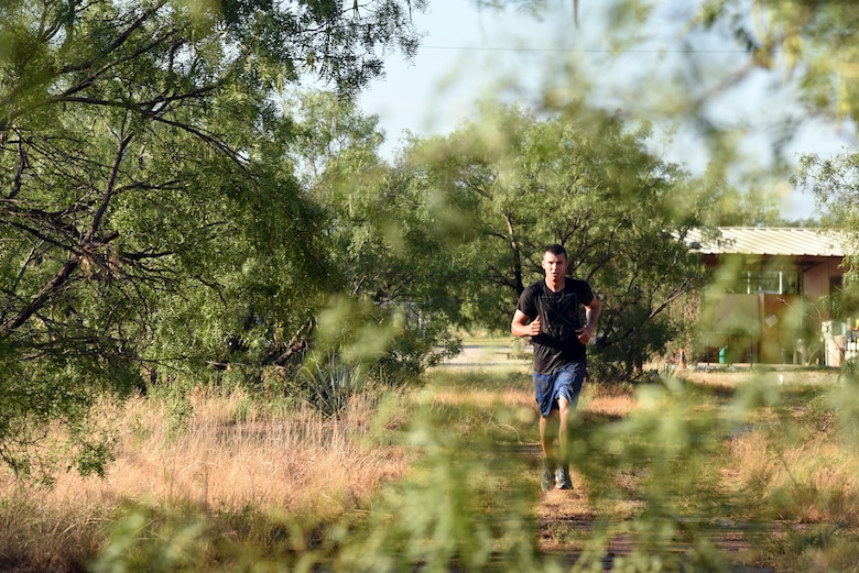 U.S. Army Pvt. Conner McCage, 344th Military Intelligence Battalion trainee, runs through a wooded area during the 344th MI BN mud run near the Camp Sentinel training area on Goodfellow Air Force Base, Texas, July 7, 2018. The mud run consisted of a 2.2 mile course and featured several obstacles. (U.S. Air Force photo by Staff Sgt. Joshua Edwards/Released)