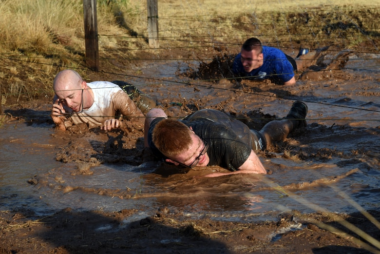 U.S. Army Pvt. Conner McCage, 344th Military Intelligence Battalion trainee, leads some other soldiers through a low crawl during the 344th MI BN mud run at the Camp Sentinel training area on Goodfellow Air Force Base, Texas, July 7, 2018. This was the 344th MI BN's first ever mud run. (U.S. Air Force photo by Staff Sgt. Joshua Edwards/Released)