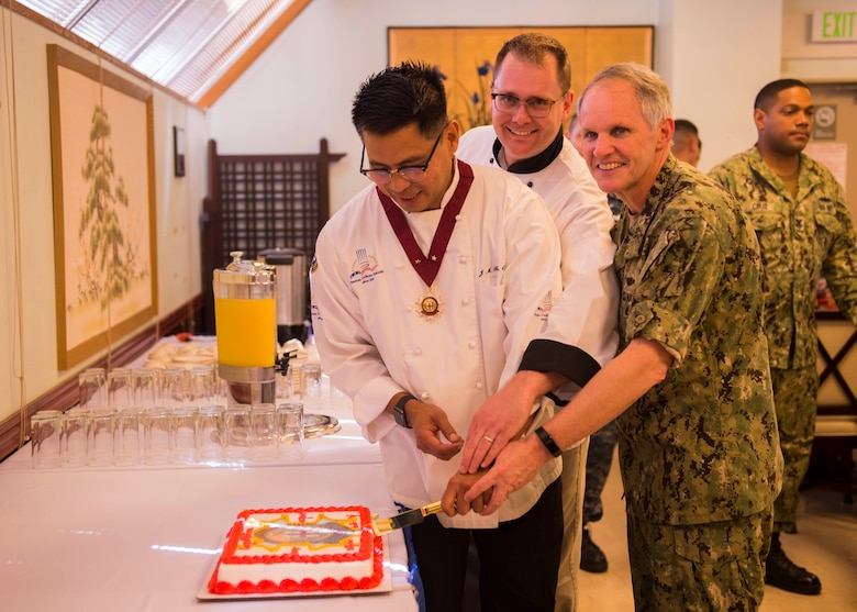YOKOSUKA, Japan -- (July 10, 2018) Senior Chief Culinary Specialist Jerome Feliciano, left, Chief Culinary Specialist Sean Zugsmith, center, and Vice Adm. Phillip G. Sawyer, commander of U.S.  7th Fleet, Culinary Excellence from the World Master Chef Society at the Jewel of the East Galley on board U.S. Fleet Activities (FLEACT) Yokosuka, Japan, July 10, 2018. The World Master Chefs Society selected Feliciano to receive the Master Chefs Diploma of Culinary Excellence in July, making him the fifth active duty enlisted service member to receive the honor in the history of Department of Defense.