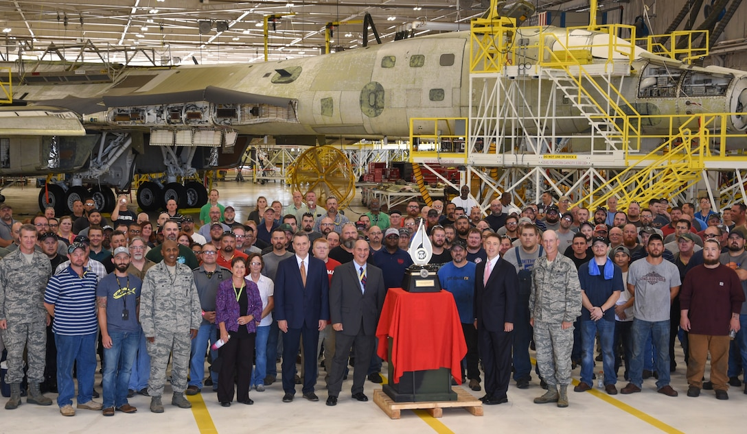 Senior leaders from the Department of Defense and Oklahoma City Air Logistics Complex stand near the Robert T. Mason trophy along with workers following the formal presention to the 567th Aircraft Maintenance Squadron on June 27, 2018, Tinker Air Force Base, Oklahoma. The 567th was recognized for their work on the ongoing B-1B Integrated Battle Station upgrades.