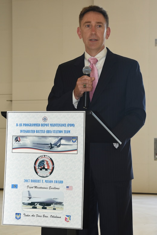 Ken Watson, Assistant Secretary of Defense for Maintenance, Policy and Programs, speaks from the podium inside hangar 2122 as he presents the Robert T. Mason award to the 567th Aircraft Maintenance Squadron on June 27, 2018, Tinker Air Force Base, Oklahoma. The 567th AMXS received the award for their work on the B-1B Programmed Depot Maintenance Integrated Battle Station upgrades.