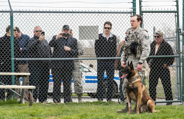 Karlo, a 436th Security Forces Squadron military working dog, sits next to Staff Sgt. David Bischoff, 436th SFS MWD handler during a training demonstration, April 11, 2018, at Dover Air Force Base, Del. Joey Logano, driver of the No. 22 Ford in the Monster Energy NASCAR Cup Series, watched Karlo, an 80-pound Belgian Malinois MWD, wait for the command to attack from Bischoff. (U.S. Air Force photo by Roland Balik)