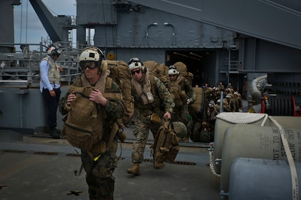 U.S. Marines board a helicopter on USS Gunston Hall.