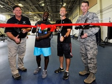 Col. Jeff Nelson, right, 628th Air Base Wing commander, and Steve Parrish, left, 628th Force Support Squadron Fitness and Sports Center director, celebrate improvements made to the Air Base fitness center with Staff Sgt. Malik Khaalis, center left, 315th Maintenance Squadron, and Master Sgt. Seth Gressley, 437th MXS, during a ribbon cutting ceremony here, July 9, 2018. The ceremony highlighted the opening of the center's functional fitness room and upgraded men's showers. The 628th FSS invested more than $700,000 in new fitness equipment and renovated the open bay shower area into nine individual custom showers.