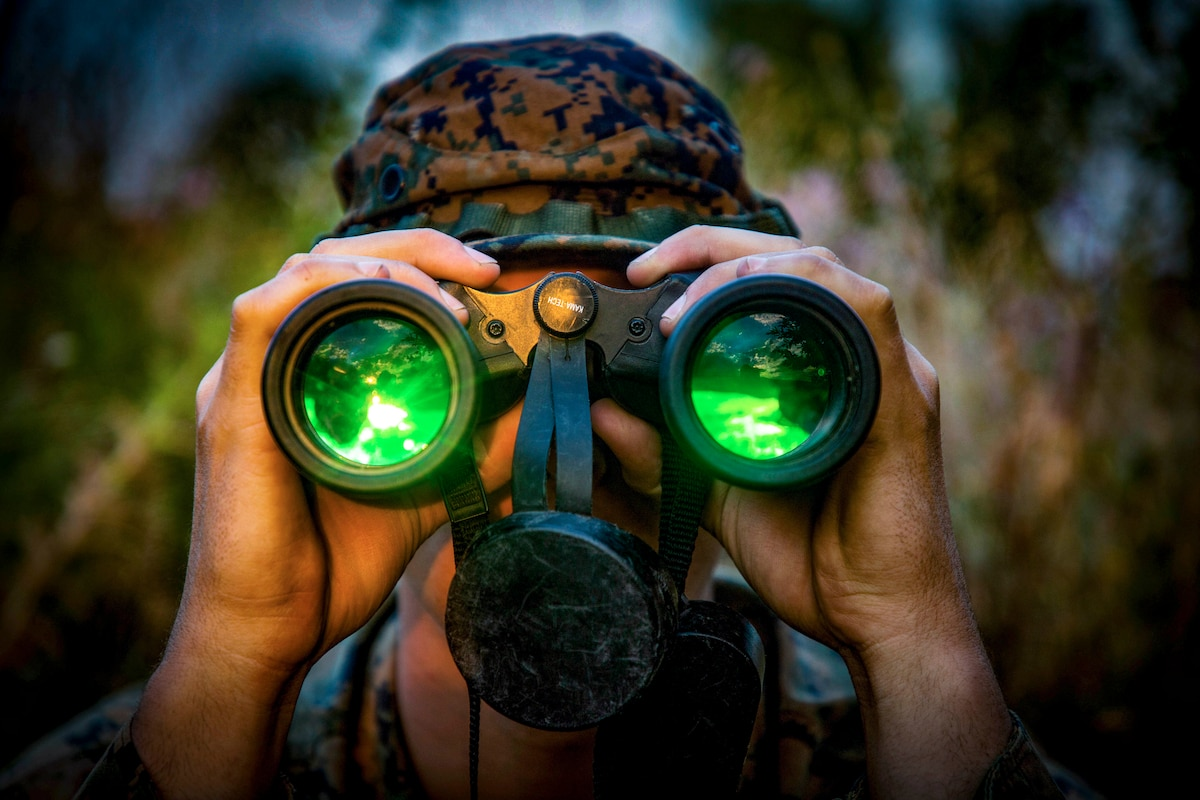 A Marine looks through binoculars with green lenses.