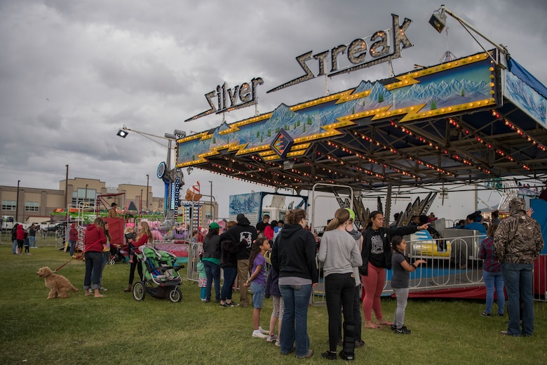 Participants wait in line for an amusement ride during the 3rd annual Summer Fest hosted by the 673d Force Support Squadron at Joint Base Elmendorf-Richardson, Alaska, July 8, 2018. The event was open to anyone with base access and offered free activities such as carnival rides, a petting zoo, face painting, a bungee trampoline, and carnival games.