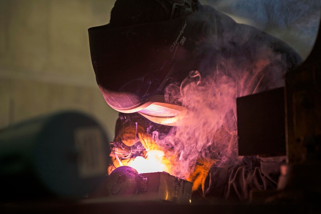 A man welds a piece of metal.