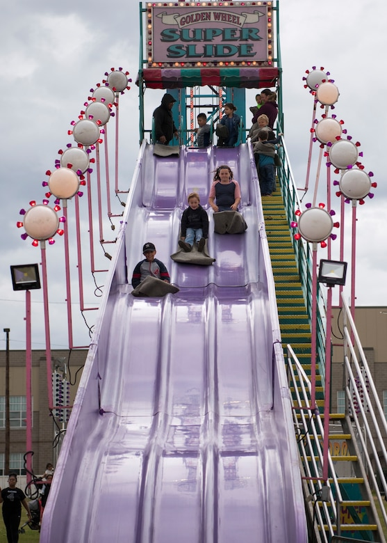 "Children ride the ""Golden Wheel Super Slide"" during the 3rd annual Summer Fest hosted by the 673d Force Support Squadron at Joint Base Elmendorf-Richardson, Alaska, July 8, 2018. The event was open to anyone with base access and offered free activities such as carnival rides, a petting zoo, face painting, a bungee trampoline, and carnival games."