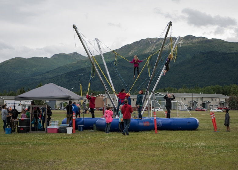 Children bounce on the bungee trampolines during the 3rd annual Summer Fest hosted by the 673d Force Support Squadron at Joint Base Elmendorf-Richardson, Alaska, July 8, 2018. The event was open to anyone with base access and offered free activities such as carnival rides, a petting zoo, face painting, a bungee trampoline, and carnival games.