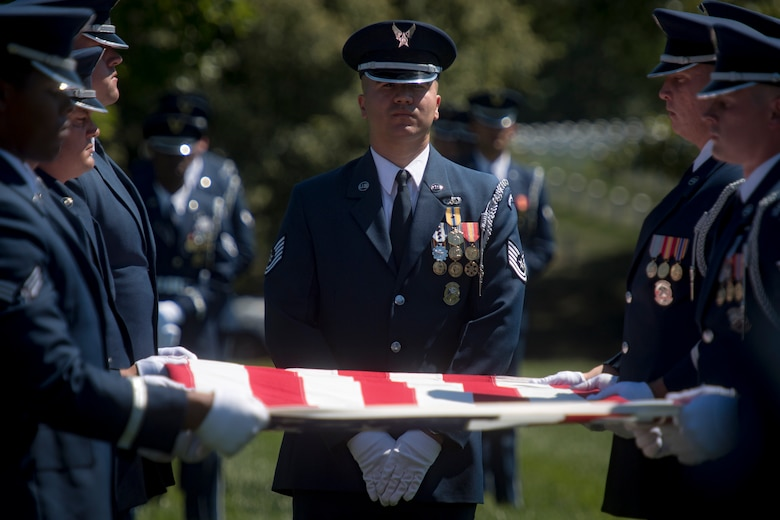 Members of the U.S. Air Force Honor Guard prepare to fold the flag above Capt. Mark Weber's casket during his funeral service, July 9, 2018, at Arlington National Cemetery, Va. Weber, a 38th Rescue Squadron combat rescue officer and Texas native, was killed in an HH-60G Pave Hawk crash in Anbar Province, Iraq, March 15. Friends, family, and Guardian Angel Airmen traveled from across the U.S. to attend the ceremony and pay their final respects. (U.S. Air Force photo by Staff Sgt. Ryan Callaghan)