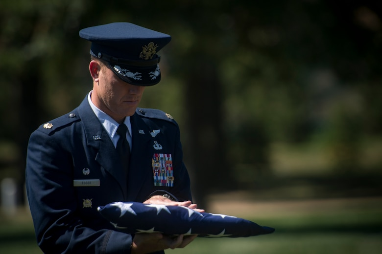 Maj. Jason Egger, 38th Rescue Squadron commander, carries a folded flag during a funeral service for Capt. Mark Weber, July 9, 2018, at Arlington National Cemetery, Va. Weber, a 38th RQS combat rescue officer and Texas native, was killed in an HH-60G Pave Hawk crash in Anbar Province, Iraq, March 15. Friends, family, and Guardian Angel Airmen traveled from across the U.S. to attend the ceremony and pay their final respects. (U.S. Air Force photo by Staff Sgt. Ryan Callaghan)