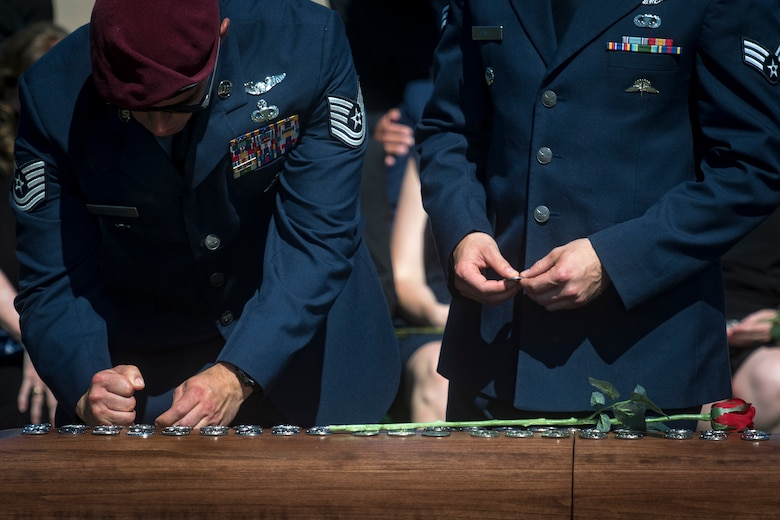 Pararescuemen pound their beret flashes into Capt. Mark Weber's casket during his funeral service, July 9, 2018, at Arlington National Cemetery, Va. Weber, a 38th Rescue Squadron combat rescue officer and Texas native, was killed in an HH-60G Pave Hawk crash in Anbar Province, Iraq, March 15. Friends, family, and Guardian Angel Airmen traveled from across the U.S. to attend the ceremony and pay their final respects. (U.S. Air Force photo by Staff Sgt. Ryan Callaghan)