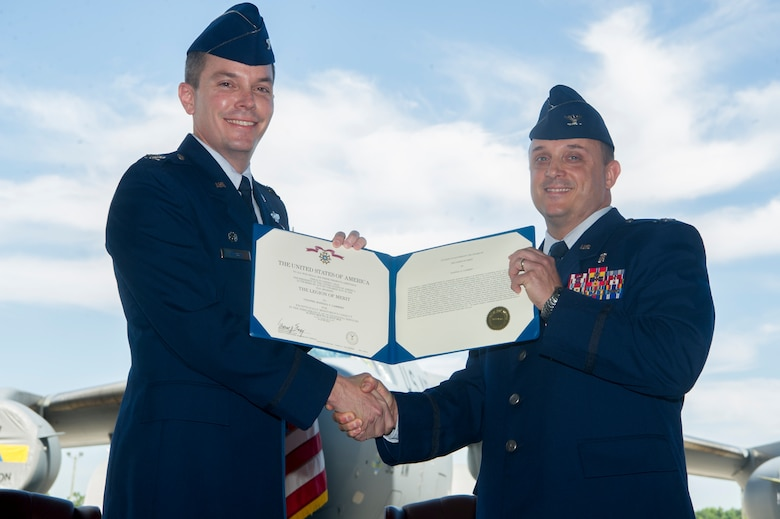 Col. Jeffrey Nelson, left, 628th Air Base Wing commander, presents Col. Craig Lambert with the Legion of Merit for his outstanding contributions as the 628th Medical Group commander during a change of command ceremony July, 10, 2018 in Nose Dock 2. The change of command ceremony provides an opportunity for subordinates to witness the formal transfer of total responsibility, authority and accountability from one officer to the next.