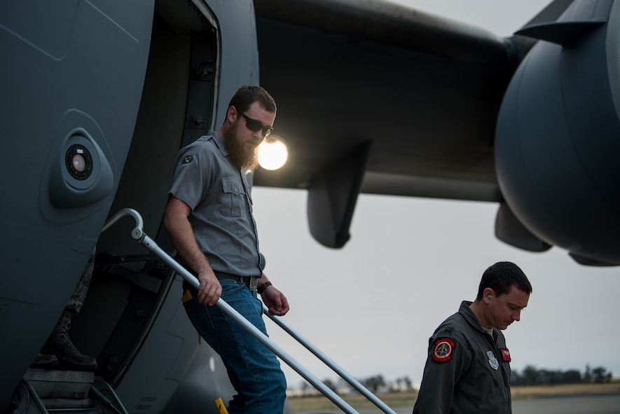 Matt Stevens, left, a U.S. Department of Agriculture airport biologist, and U.S. Air Force Capt. Sean Harte, 60th Air Mobility Wing Safety Office flight commander, go over C-17 Globemaster III pre-flight procedures before a safety familiarization flight at Travis Air Force Base, Calif., July 2, 2018. The flight allowed Stevens, who helps manage the Bird/Wildlife Aircraft Strike Program at Travis to get a firsthand view of what pilots see during training flights near the base. (U.S. Air Force photo by Master Sgt. Joey Swafford)