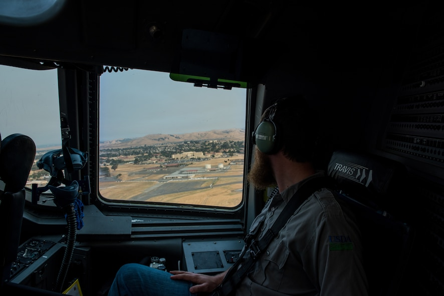 Matt Stevens, a U.S. Department of Agriculture airport biologist, looks out the window of a C-17 Globemaster III after taking off from Travis Air Force Base, Calif., July 2, 2018. The flight allowed Stevens, who helps manage the Bird/Wildlife Aircraft Strike Program at Travis to get a firsthand view of what pilots see during training flights near the base. (U.S. Air Force photo by Master Sgt. Joey Swafford)
