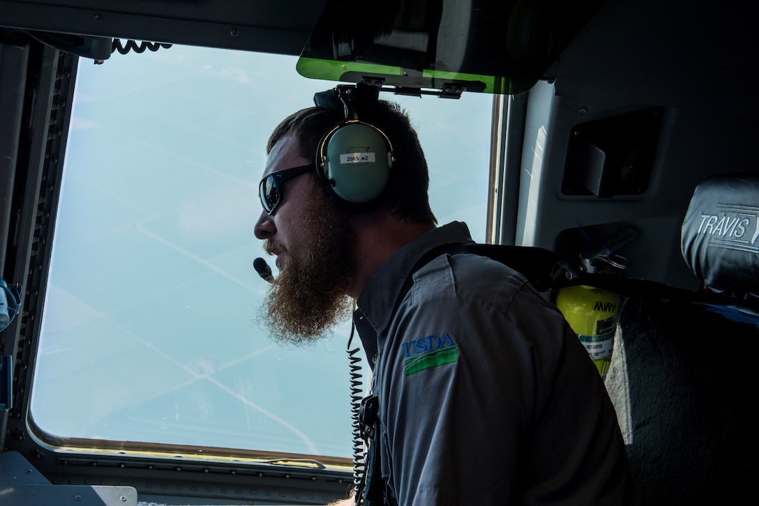 Matt Stevens, a U.S. Department of Agriculture airport biologist, looks for possible bird congregation areas during a C-17 Globemaster III low level flight over California July 2, 2018. The flight allowed Stevens, who helps manage the Bird/Wildlife Aircraft Strike Program at Travis Air Force Base, Calif., to get a firsthand view of what pilots see during training flights near the base. (U.S. Air Force photo by Master Sgt. Joey Swafford)