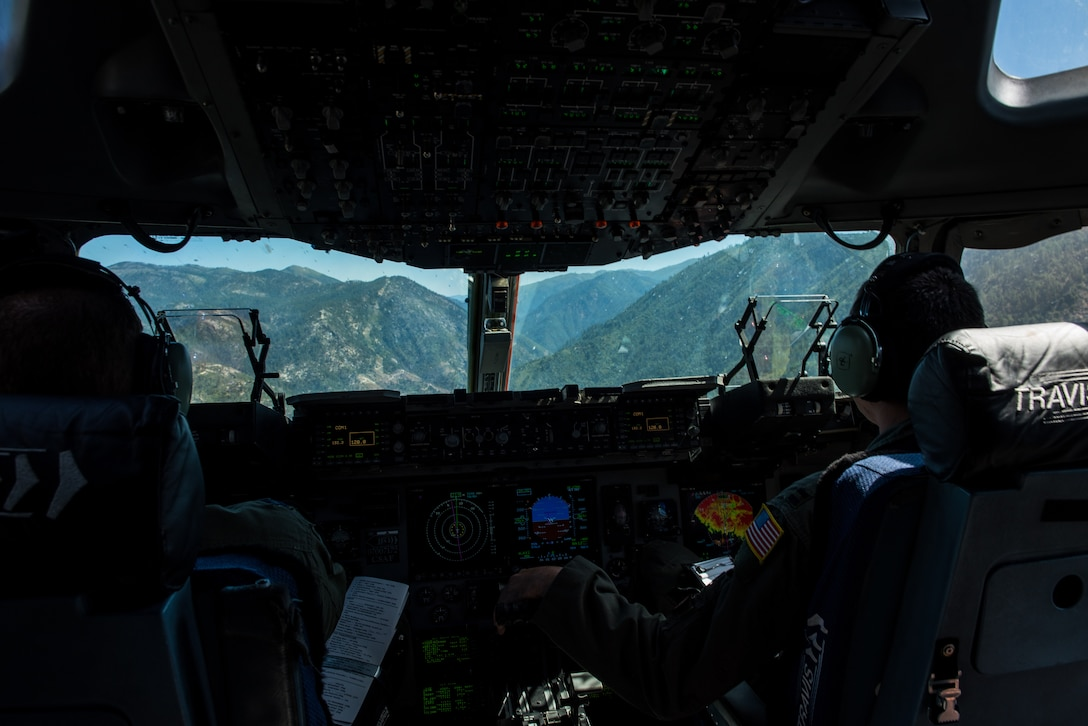 U.S. Air Force Capt. Sean Harte, right, 60th Air Mobility Wing Safety Office flight commander, and Capt. Doc Schumacher, 21st Airlift Squadron C-17 Globemaster III pilot, fly a C-17 over California during a safety office familiarization flight, July 2, 2018. The flight allowed Matt Stevens, a U.S. Department of Agriculture airport biologist, who helps manage the Bird/Wildlife Aircraft Strike Program at Travis Air Force Base, Calif., to get a firsthand view of what pilots see during training flights near the base. (U.S. Air Force photo by Master Sgt. Joey Swafford)