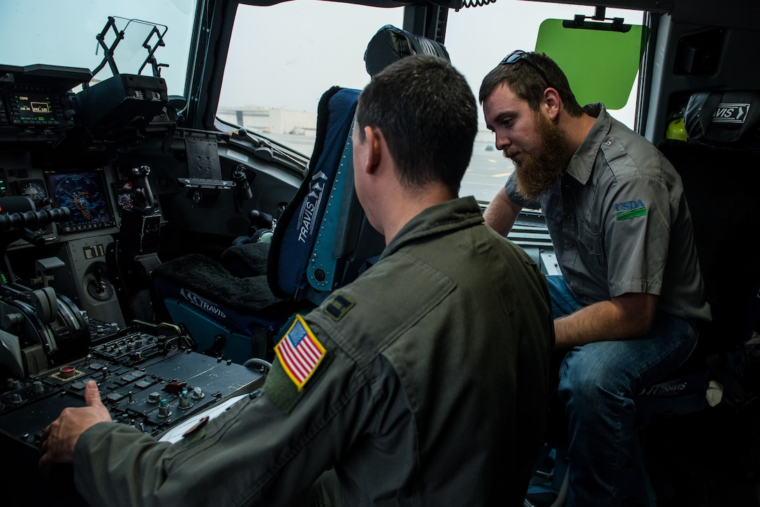 Matt Stevens, right, a U.S. Department of Agriculture airport biologist, and U.S. Air Force Capt. Sean Harte, 60th Air Mobility Wing Safety Office flight commander, go over C-17 Globemaster III pre-flight procedures at Travis Air Force Base, Calif., July 2, 2018. The flight allowed Stevens, who helps manage the Bird/Wildlife Aircraft Strike Program at Travis get a firsthand view of what the pilots see during training flights near the base. (U.S. Air Force photo by Master Sgt. Joey Swafford)