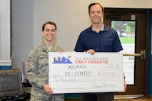 Kraig Hanson, Director of Hill Air Force Base Family Foundation, hands a donation check for the Airman Recreation Center to Airman 1st Class Allison West, who is President of the Hill First Four. The recreation center is in