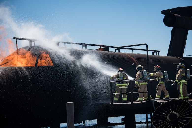 Firefighters with the 137th Special Operations Wing Fire and Emergency Services, Oklahoma City, and the 138th Fighter Wing Fire Department, Tulsa, Oklahoma, cool a metal aircraft structure before entering to attack an interior fire during deployment readiness training at March Air Reserve Base in Riverside County, California, June 28, 2018. The 137th Special Operations Civil Engineering Squadron members train at a regional training site every three years as a part of this deployment readiness training. (U.S. Air National Guard photo by Staff Sgt. Brigette Waltermire)
