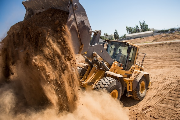 Airman 1st Class Kevin Coulter, a pavement and heavy equipment operator with the 137th Special Operations Civil Engineering Squadron (137th SOCES), Oklahoma City, dumps a scoop of dirt from a loader during deployment readiness training at March Air Reserve Base in Riverside County, California, June 26, 2018. The 137th SOCES members train at a regional training site every three years as a part of this deployment readiness training. (U.S. Air National Guard photo by Staff Sgt. Brigette Waltermire)