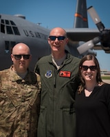 """U.S. Air Force Col. Timothy Stumbaugh, center, the commander of the 182nd Maintenance Group, Illinois Air National Guard, poses for a photo with Master Sgt. Jakob Pogeman and his spouse after Stumbaugh's """"fini flight"""" in Peoria, Illinois, June 4, 2018."""