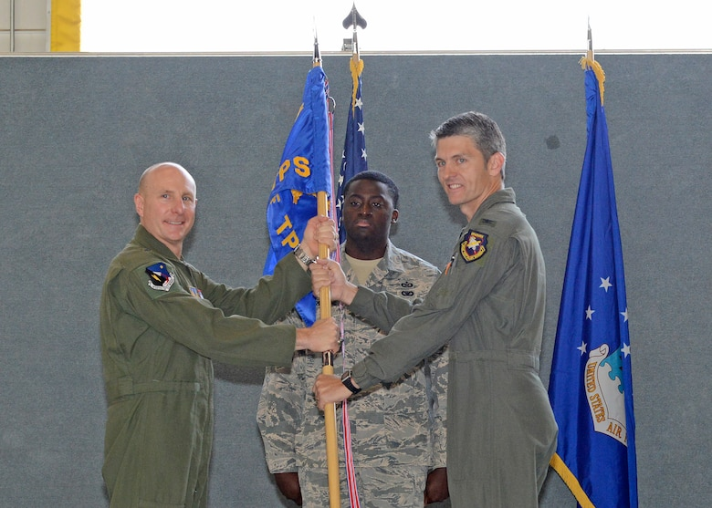 Brig. Gen. Carl Schaefer, 412th Test Wing commander (left), and new U.S. Air Force Test Pilot School commandant, Col. Ryan Blake, pose with the school's guidon during a change of command ceremony in Hangar 1207 July 10. (U.S. Air Force photo by Kenji Thuloweit)