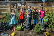 Children from the Survival, Evasion, Resistance and Escape Kids' Garden Club pose for a photo July 09, 2018 at Fairchild Air Force Base, Washington. With the intention to grow a variety of fruits and vegetables, as well as a community with each other, the SERE Kids Garden Club has grown to include ten SERE families, all sharing in the tasks of maintaining the garden.