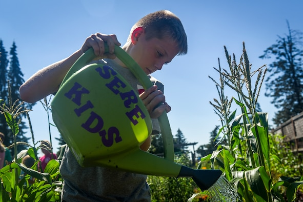 Member of the Survival, Evasion, Resistance and Escape Kids' Garden Club waters the rows of produce July 09, 2018 at Fairchild Air Force Base, Washington. Each family rotates on a weekly cycle, bringing their kids to grow, learn and make memories throughout the process. (U.S. Air Force photo/ Airman 1st Class Whitney Laine)