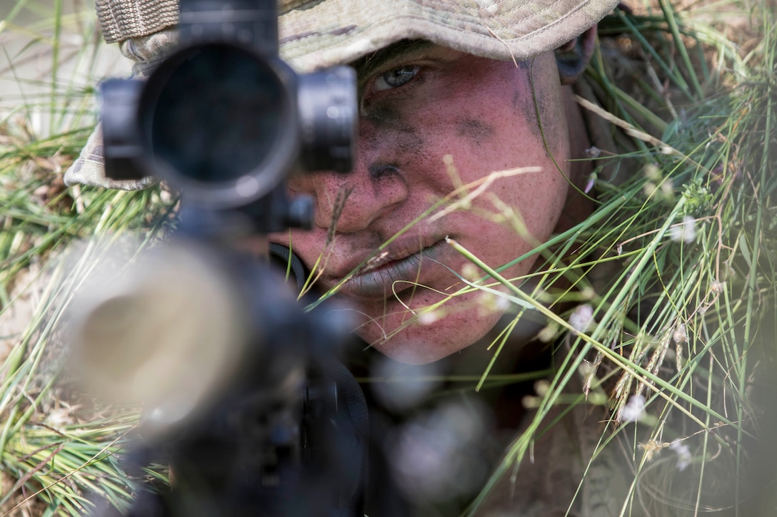 A soldier stares through a rifle scope.