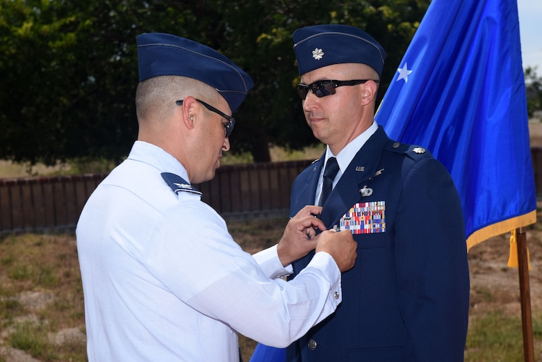 Col. Curtis Hernandez, 30th Operations Group commander, presents the meritorious service medal to Lt. Col. Max Coberly, 30th Range Management Squadron commander, at Vandenberg Air Force Base, Calif., on July 10, 2018. Coberly was presented the medal shortly after the inactivation of the 30th RMS. (U.S. Air Force photo by Tech. Sgt. Jim Araos/Released)