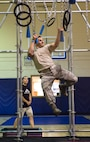 A U.S. Air Force Airman hangs as best he can as part of the Alpha Warrior Challenge at RAF Alconbury, Juy 10, 2018. The Challenge had over 10 difficult obstacles to overcome to earn the title alpha warrior. (U.S. photo by Senior Airman Chase Sousa)