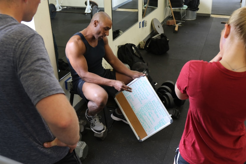 A trainer explains a fitness routine written on a whiteboard.