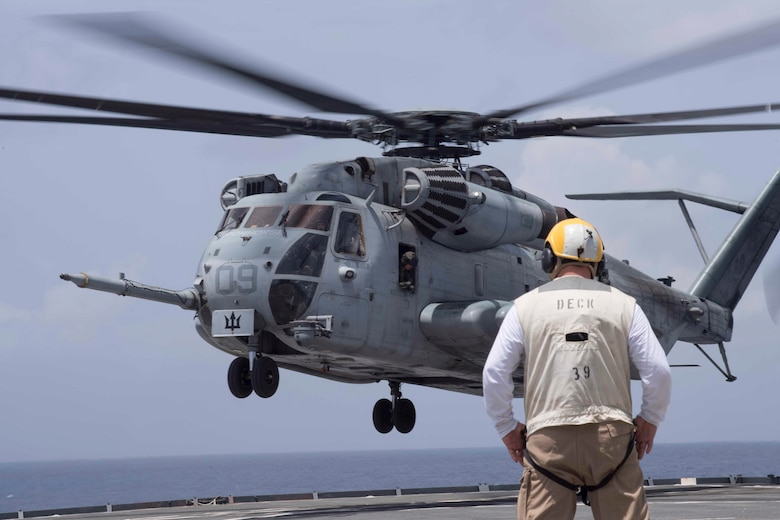 A U.S. Navy sailor watches as a CH-53E Super Stallion helicopter with Special Purpose Marine Air-Ground Task Force - Southern Command comes in for a landing on the flight deck of the USS Gunston Hall while conducting deck landing qualification training off the coast of Belize, July 7, 2018. The Marines of SPMAGTF-SC worked closely with Gunston Hall sailors to qualify six pilots and five enlisted aircrew members responsible for the helicopters' safe operation. Having qualified Marines provides SPMAGTF-SC with helicopter movement capabilities of personnel and cargo between the shore and ship. The Marines and sailors of SPMAGTF-SC are conducting security cooperation training and engineering projects alongside partner nation military forces in Central and South America. The unit is also on standby to provide humanitarian assistance and disaster relief in the event of a hurricane or other emergency in the region.