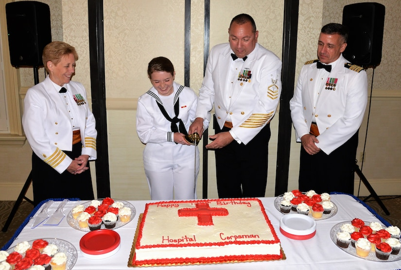 Navy Seaman Katlin Dowling, center left, a hospital apprentice serving at Naval Health Clinic Charleston, and NHCC Command Master Chief Anthony Petrone, center right, cut the cake during NHCC's Hospital Corpsman Ball, celebrating the 120th birthday of the US Navy Hospital Corps. Standing by are NHCC Executive Officer Capt. Kathleen Hinz, far left, and NHCC Commanding Officer Capt. Dale Barrette, far right.