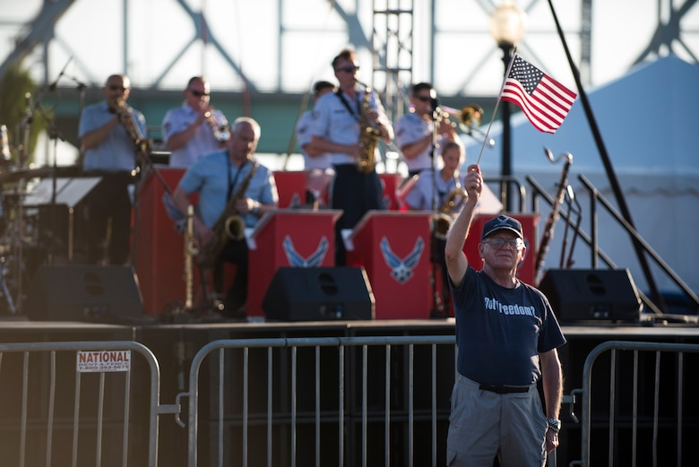 Man holding flag in front of stage where Jazz ensemble is  playing