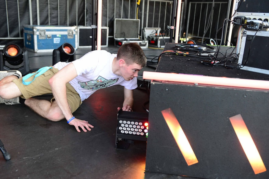 Airman 1st Class Anthony Connors, 14th Force Support Squadron personnelist, hooks up lights on stage July 6, 2018, on Columbus Air Force Base, Mississippi. Air Force Entertainment and participating bases agreed that base personnel would provide volunteers to assist the stage crew in setting up and running the event. (U.S. Air Force photo by Airman 1st Class Beaux Hebert)