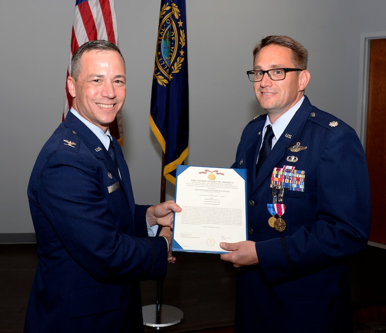 Lt. Col. Joshua J. Zaker, commander of the 64th Air Refueling Squadron, receives a Meritorious Service Medal certificate from Col. Robert L. Hanovich JR, commander of the 22nd Operations Group at McConnell Air Force Base, Kan. during a ceremony on July 6, 2018 at Pease Air National Guard Base, N.H. Zaker relinquished command of the 64th ARS after more than three years as the commander. (N.H. Air National Guard photo by Staff Sgt. Kayla White)