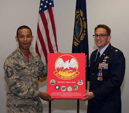 Lt. Col. Joshua J. Zaker, commander of the 64th Air Refueling Squadron, receives a gift from Master Sgt. Fernando B. Reyes, superintendent of the 64th Operations Support Flight, during a ceremony on July 6, 2018 at Pease Air National Guard Base, N.H. Zaker relinquished command of the 64th ARS after more than three years as the commander. (N.H. Air National Guard photo by Staff Sgt. Kayla White)