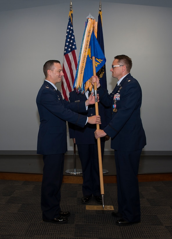 Lt. Col. Joshua J. Zaker, commander of the 64th Air Refueling Squadron, passes the 64th ARS guidon to Col. Robert L. Hanovich JR, commander of the 22nd Operations group at McConnell Air Force Base, Kan. during a ceremony on July 6, 2018 at Pease Air National Guard Base, N.H. Zaker relinquished command of the 64th ARS after more than three years as the commander. (N.H. Air National Guard photo by Staff Sgt. Kayla White)
