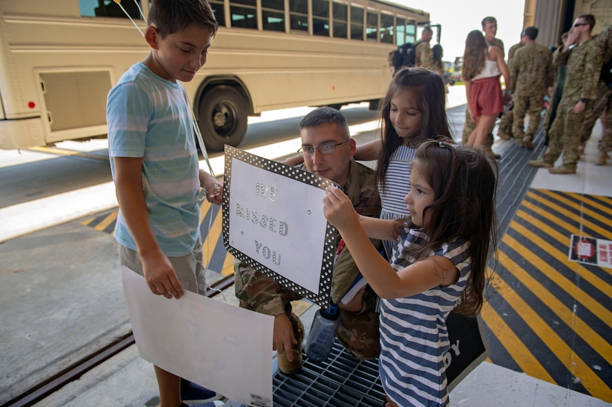 Senior Master Sgt. Alejandro Munoz, 723d Aircraft Maintenance Squadron superintendent, reunites with his family during a 41st Rescue Squadron redeployment ceremony, July 10, 2018, at Moody Air Force Base, Ga.  While deployed, the 41st RQS and 41st Helicopter Maintenance Unit provided combat search and rescue capabilities and maintenance operations in support of Combined Joint Task Force-Horn of Africa. (U.S Air Force photo by Senior Airman Greg Nash)