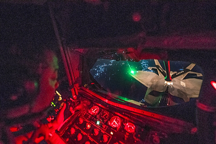 An airman looks out a window toward an aircraft in flight.