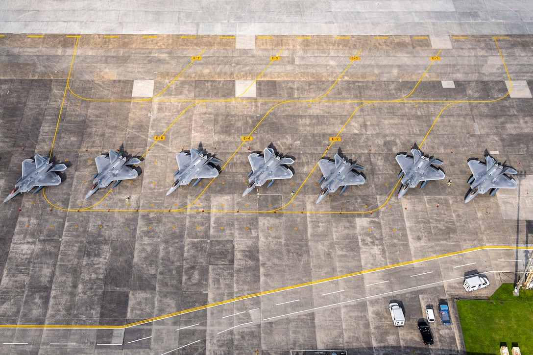 A line of aircraft sit on a flat surface..