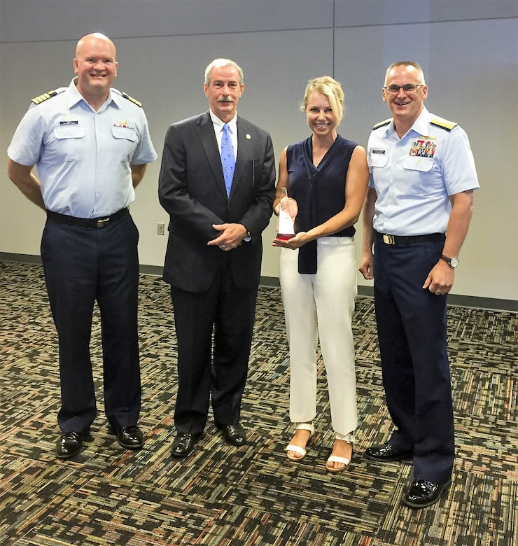 Capt. John Reed, left, Commanding Officer of Sector Charleston, Mark Keel, Chief of the South Carolina Law Enforcement Division (SLED), Heather Holmquest, President of the Maritime Association of South Carolina, and Rear Adm. John Nadeau, right, Assistant Commandant for Prevention Policy, stand together, Monday, July 9, 2018, during a recognition ceremony for the Charleston Area Maritime Security Committee (AMSC) at the International Longshoreman's Association building in Charleston, S.C.
