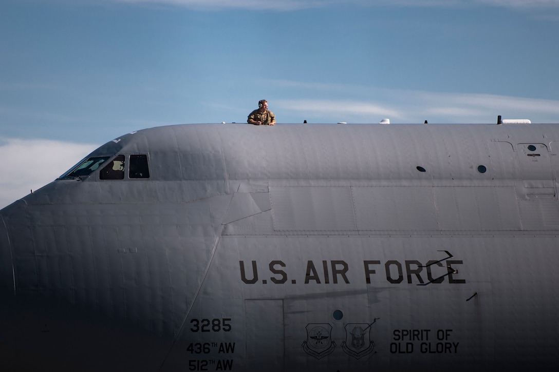An Airman looks out onto the flightline on top of a C-5 Galaxy during the 41st Rescue Squadron's (RQS) redeployment ceremony, July 10, 2018, at Moody Air Force Base, Ga. While deployed, the 41st RQS and the 41st Helicopter Maintenance Unit provided combat search and rescue capabilities and maintenance operations in support of Combined Joint Task Force-Horn of Africa. (U.S. Air Force photo by Airman Taryn Butler)