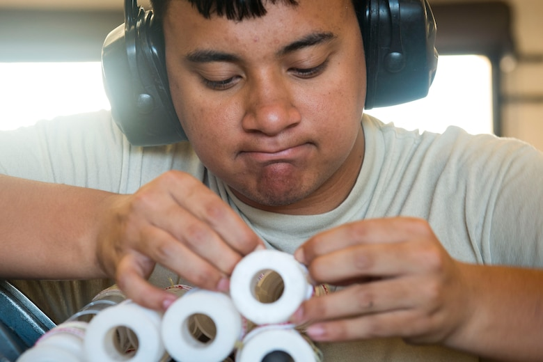 Airman 1st Class Jordan Sili, 23d Maintenance Squadron (MXS) crew member, ties linked tube carriers together during a 30mm rounds processing, July 11, 2018, at Moody Air Force Base, Ga. This total force integration training with the 23d and 476th MXS allowed Airmen to work together to identify more ways to efficiently and safely conduct their mission. The munitions flight ensures the A-10C Thunderbolt IIs are armed with 30mm rounds to make sure they are able to continue their mission while at home station and deployed. (U.S. Air Force photo by Airman 1st Class Erick Requadt)