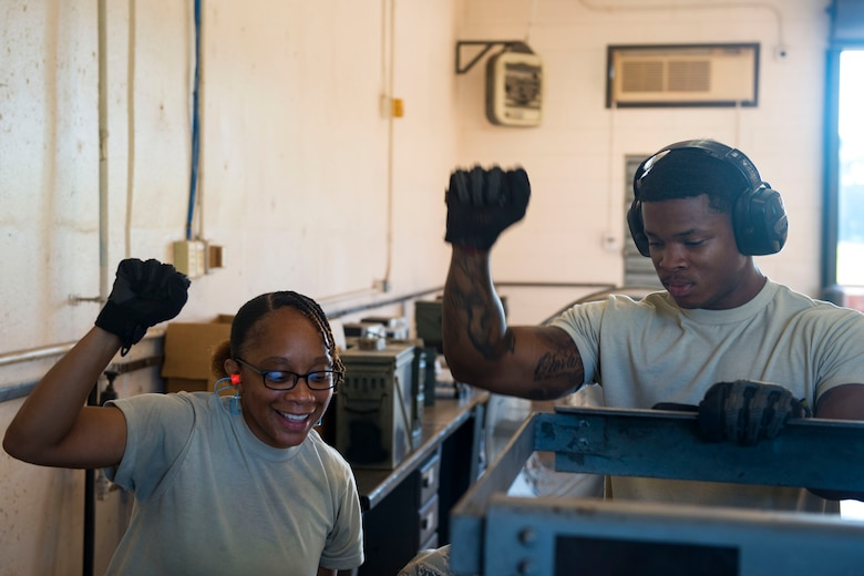 Senior Airman Kimberly Daniel, left, 476th Maintenance Squadron (MXS) crew chief, and Senior Airman Darious Johnson, 23d MXS crew chief, signal to stop a GFU-7 rail system during a 30mm rounds processing, July 11, 2018, at Moody Air Force Base, Ga. This total force integration training with the 23d and 476th MXS allowed Airmen to work together to identify more ways to efficiently and safely conduct their mission. The munitions flight ensures the A-10C Thunderbolt IIs are armed with 30mm rounds to make sure they are able to continue their mission while at home station and deployed. (U.S. Air Force photo by Airman 1st Class Erick Requadt)