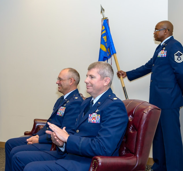 U.S. Air Force Lt. Col. Jerry Hambright, outgoing 81st Communications Squadron commander, and Maj. Jon Drummond, incoming 81st CS commander, participate in the 81st CS change of command ceremony in the Roberts Consolidated Aircraft Maintenance Facility Auditorium at Keesler Air Force Base, Mississippi, June 28, 2018. The passing of the guidon is a ceremonial symbol of exchanging command from one commander to another. (U.S. Air Force photo by Andre' Askew)